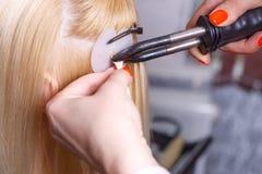 头发引伸做法 美发师对头发引伸做女孩,白肤金发在美容院 选择聚焦 免版税库存照片