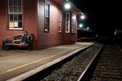 发抖在火车站的孤独的妇女 免版税图库摄影