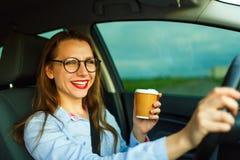 发正文消息和喝咖啡w的年轻女实业家 免版税库存图片