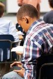 发正文消息的公学生在教室 免版税库存照片