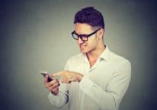 发正文消息的沮丧的年轻人使用手机 免版税图库摄影