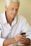 发正文消息的老人坐沙发 免版税库存照片