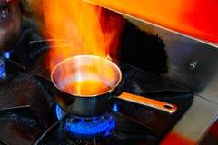 发火焰烹调平底锅在餐馆厨房里 图库摄影