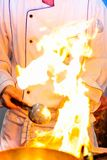 发火焰烹调,火烧伤烹调在铁平底锅, restaur的厨师 免版税库存图片
