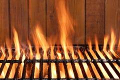发火焰BBQ木炭生铁格栅和木头背景 免版税图库摄影