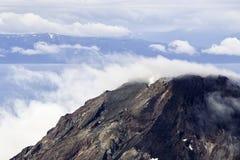 发烟性云彩围拢的阿拉斯加的峰顶 免版税库存照片