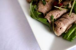 发牢骚与芝麻菜的肉卷在白色台式 免版税库存图片