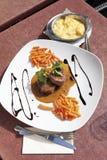 发牢骚内圆角用胡椒奶油沙司和红萝卜,土豆 免版税图库摄影