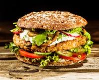 发牢骚在一个健康整粒小圆面包的汉堡 免版税库存照片