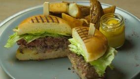 发牢骚在芝麻籽小圆面包的汉堡包膳食冠上用烟肉和乳酪和供食用酥脆炸薯条 股票视频
