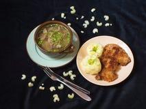 发牢骚汤用饺子、土豆泥和vienesse shnitzel,芹菜,黑背景茎片断  免版税库存图片