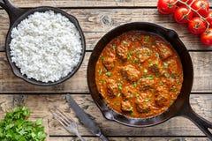 发牢骚马都拉斯咖喱慢厨师印地安辣辣椒羊羔食物用在生铁平底锅的米 免版税库存照片