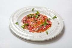 发牢骚carpaccio装饰与在白色板材的新鲜的芝麻菜 免版税库存照片