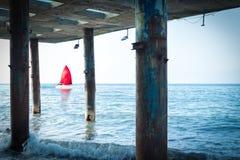 发现、希望和旅行的概念-有一个红色风帆的一条风船由海漂浮 从码头的老柱子的看法 库存照片