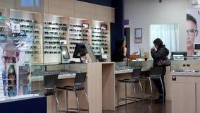发现一块适当的玻璃的女性眼镜师对顾客 影视素材