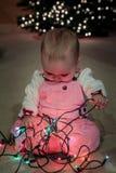 发现圣诞灯串的婴孩 免版税库存图片