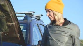 发现在她的SUV的一个白肤金发的女孩一个缺点离开汽车并且打开敞篷 外部看法 影视素材