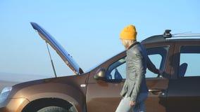 发现在她的SUV的一个白肤金发的女孩一个缺点离开汽车并且打开敞篷 外部看法 股票录像