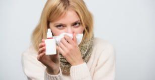 发现安心浪花  病的妇女喷洒的疗程到鼻子里 有鼻涕的不适的女孩使用鼻孔喷射 免版税库存照片