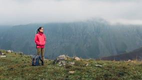 发现旅行目的地冒险概念 有背包上升的年轻徒步旅行者妇女在与拷贝空间的山上面 库存图片