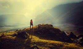 发现旅行目的地概念 有背包的远足者妇女在山上面起来反对被定调子的日落葡萄酒背景 免版税库存照片
