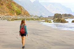 发现狂放的天堂海滩的年轻女性徒步旅行者在特内里费岛 后面看法旅客女孩在暗藏的惊人的海滩到达 库存图片