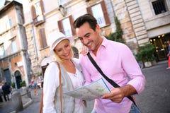 发现罗马在地图帮助下的游人  库存图片