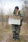 发现自然的伪装成套装备的年轻美丽的妇女在有指南针和地图的森林里 旅行生活方式概念 免版税库存图片