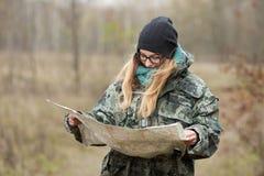 发现自然的伪装成套装备的年轻美丽的妇女在有指南针和地图的森林里 旅行生活方式概念 免版税库存照片