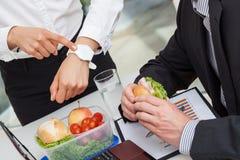 发生冲突与关于午餐时间的工作者的经理 库存照片