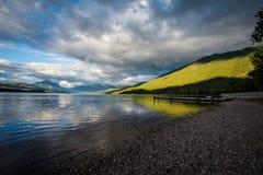 发生,饱和的太阳在湖麦当劳的一场暴雨以后偷看在冰川国家公园 免版税库存照片
