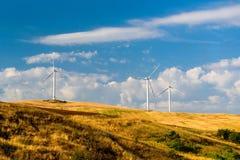 发电的风轮机在领域在蓝天下 免版税库存照片