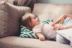 发痒她的沙发的爱恋的母亲小女孩 库存照片