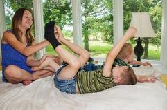 发痒笑的男孩的脚的女孩 免版税库存照片