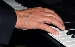发痒Ivories -弹钢琴的手特写镜头 库存图片