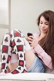 发短信与她的手机的女孩 免版税库存图片
