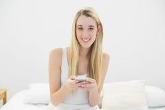 发短信与她的智能手机的可爱的白肤金发的妇女坐她的床 库存图片