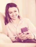 发短信与她的电话和拍照片的妇女 库存图片