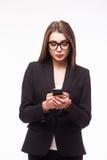 发短信与她的电话的微笑的美丽的女商人 库存照片