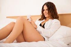 发短信与她的电话的性感的女孩 库存图片