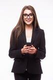 发短信与她的电话的美丽的女商人 免版税库存照片