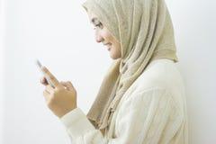 发短信与她的sm的一名微笑的美丽的回教妇女的画象 库存图片