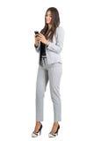 发短信与手机的年轻人微笑的正式装饰的妇女 免版税库存照片