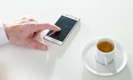 发短信与智能手机和喝咖啡的商人 免版税库存照片
