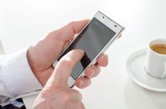 发短信与智能手机和喝咖啡的商人 库存图片