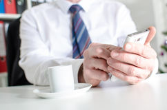 发短信与智能手机和喝咖啡的商人 免版税库存图片