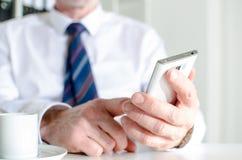 发短信与智能手机和喝咖啡的商人 库存照片