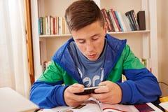 发短信与智能手机的少年,当学习时 免版税库存照片