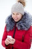 发短信与流动酸碱度的红色冬天夹克的愉快的微笑的女性 免版税库存图片