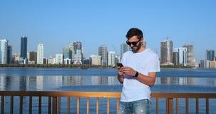 发短信使用在智能手机的应用程序的人sms在城市 使用智能手机微笑的愉快佩带的英俊的年轻商人 股票录像